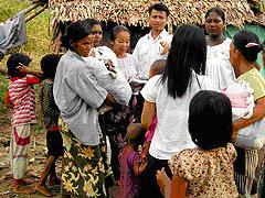 ミャンマーの救世軍士官(中央奥)がヤンゴン(ラングーン)の南にあるマギィハンという地域の家族に衣類を届ける。