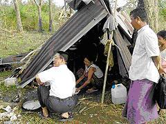 ミャンマーの救世軍士官(しゃがんでいる人)が仮小屋で生活するマギィハン地域の被災者に慰めの言葉をかける。