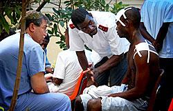 ポルトープランスのデルマで開設された診療所で、医師から患者への説明を(救世軍)南ハイチ地区の士官ロロル・クラナ大尉が通訳