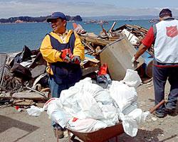 津波が襲ったカレタ・トゥンベスにて、救世軍チーム員が瓦礫の除去を手伝う。